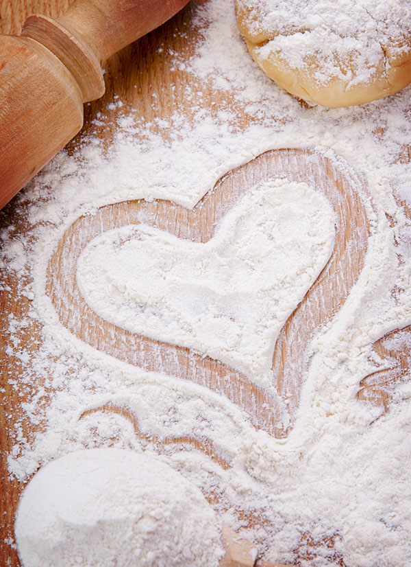 Heart drawn with flour on the kitchen table. Food ingredient